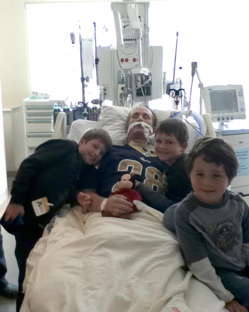 John Reynolds with his children in hospital shortly before his life support was turned off.