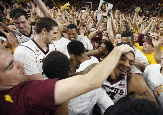 Arizona State's Jermaine Marshall, right, is surrounded by players and fans after an NCAA college basketball game win against Arizona, Friday, Feb. 14, 2014, in Tempe, Ariz. Arizona State defeated Arizona 69-66 in double overtime. (AP Photo/Ross D. Franklin)