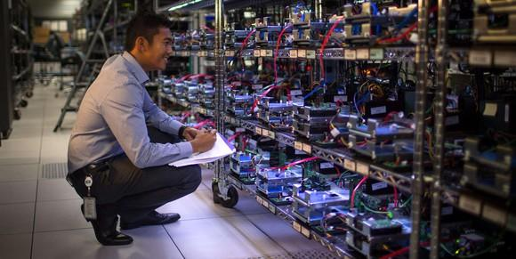 A man kneels to inspect an array of Western Digital storage drives
