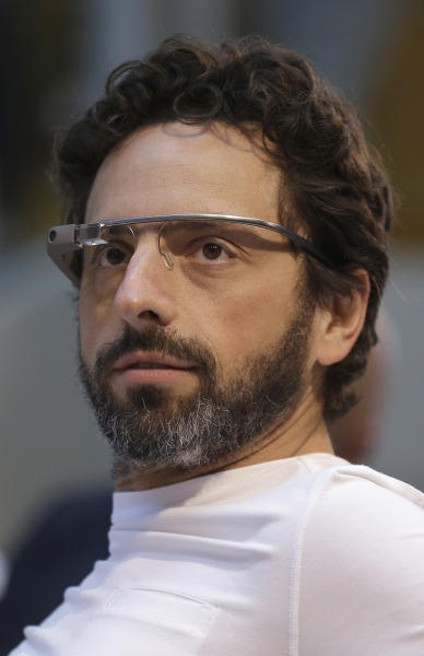 """Google co-rounder Sergey Brin, left, wears Google Glass glasses at an announcement for the Breakthrough Prize in Life Sciences at Genentech Hall on UCSF's Mission Bay campus in San Francisco, Wednesday, Feb. 20, 2013. Google is giving more people a chance to pay $1,500 for a pair of the Internet-connected glasses that the company is touting as the next breakthrough in mobile computing. The product, dubbed """"Google Glass,"""" will be offered to """"bold, creative individuals"""" selected as part of a contest announced Wednesday. Participants must live in the U.S. and submit an application of up to 50 words explaining what they would do with the Google Glass technology. (AP Photo/Jeff Chiu)"""