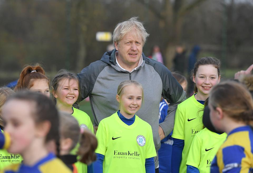 Prime Minister Boris Johnson before a football match stands with a group of junior players (PA Archive)