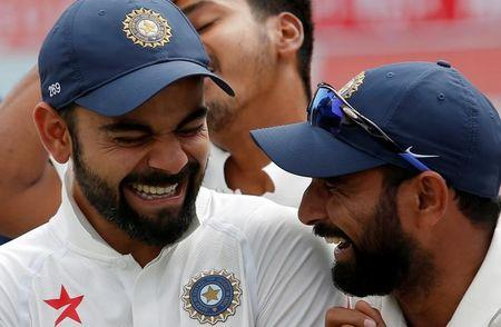 Cricket - India v Australia - Fourth Test cricket match - Himachal Pradesh Cricket Association Stadium, Dharamsala, India - 28/03/17 - India's Virat Kohli and Mohammed Shami (R) shares a moment during an award ceremony after winning the series. REUTERS/Adnan Abidi
