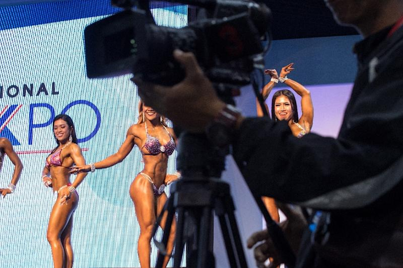 Female bodybuilder finalists pose in front of judges at a local bodybuilding competition in Bangkok, Thailand