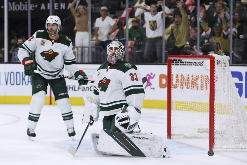 Minnesota Wild goalie Cam Talbot (33) and defenseman Ian Cole (28) react after the Vegas Golden Knights scored during the second period of Game 7 of an NHL hockey Stanley Cup first-round playoff series Friday, May 28, 2021, in Las Vegas. (AP Photo/Joe Buglewicz)