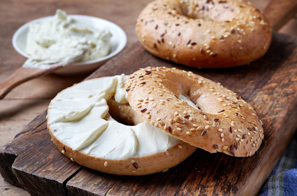 Bagel with cream cheese on wooden table