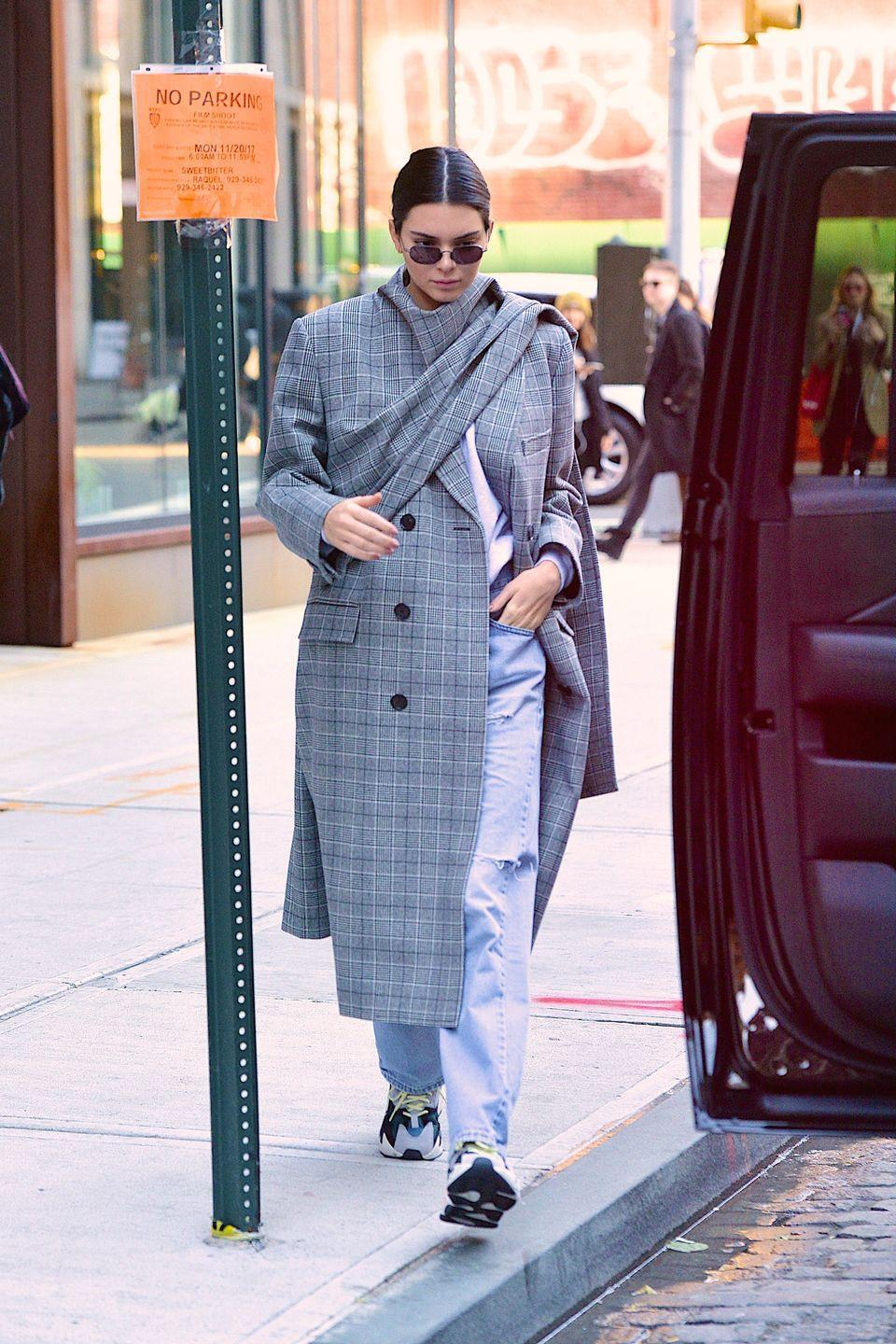 <p>Kendall Jenner works a Balenciaga plaid coat with Yeezy jeans while out and about in New York, November 2017</p>