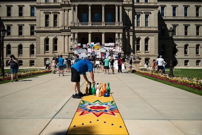"""Todd """"K"""" Kwiecien, co-owner of Royal Scot Bowling in Lansing, and others rally at the Michigan Capitol on Aug. 12, 2020, demanding that the state government allow bowling centers to open."""