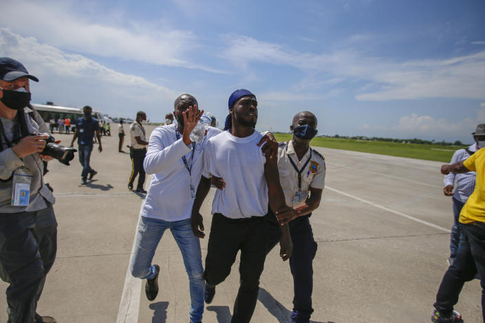 Police detain a Haitian who was deported from the United States, after he tried to board the same plane in which he was deported in, in an attempt to return to the United States, at the Toussaint Louverture airport in Port-au-Prince, Haiti Tuesday, Sept. 21, 2021 (AP Photo/Joseph Odelyn)