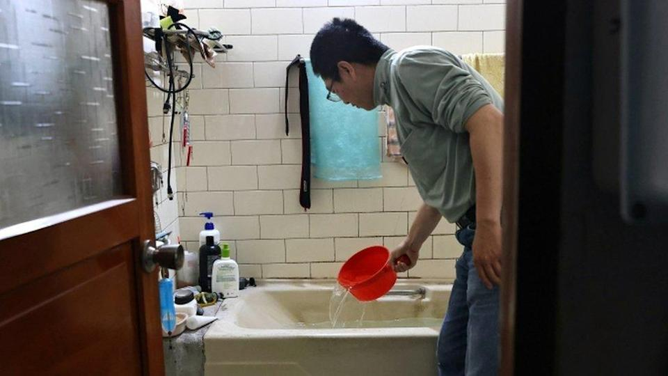 A man scoops water from a bathtub, where he stores water amid water rationing during an island-wide drought, in Hsinchu, Taiwan on March 12, 2021