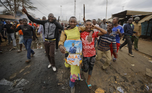 <p>A protester wearing a woman's dress as a joke, on which is pinned a banner of opposition candidate Raila Odinga, who they support, walks towards police before clashes erupted in the Kawangware area of Nairobi, Kenya Thursday, Aug. 10, 2017. (Photo: Ben Curtis/AP) </p>