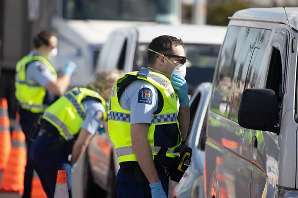 Police officers wearing protective masks talk to motorists at a checkpoint in the Bombay area of Auckland, New Zealand. The country recorded its first coronavirus community transmission cases for the first time in three months.