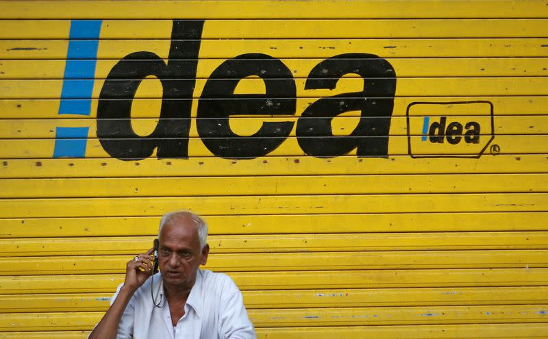FILE PHOTO: A man speaks on his mobile phone as he sits in front of a shop displaying the Idea Cellular Ltd's logo on its shutter in Mumbai