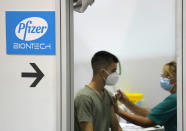 A medical worker administers a shot of Pfizer COVID-19 vaccine to a man at Belgrade Fair makeshift vaccination center in Belgrade, Serbia, Tuesday, Aug. 17, 2021. Serbia has started administering a third, or booster, dose of four different vaccines, including Sinopharm, Pfizer, Sputnik and AstraZeneca, to people who previously were vaccinated at least 6 months ago. (AP Photo/Darko Vojinovic)