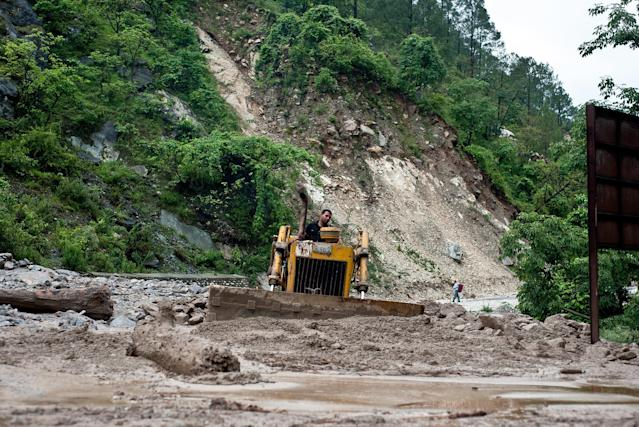 An Indian Border Roads Organisation (BRO) worker clears a landslide across the road caused by overnight rains in Gauchar on June 24, 2013. Indian priests are planning to cremate hundreds of flood victims on June 24, as heavy rains halted the search for thousands of tourists stranded in the devastated Himalayan region, officials said. AFP PHOTO/MANAN VATSYAYANA