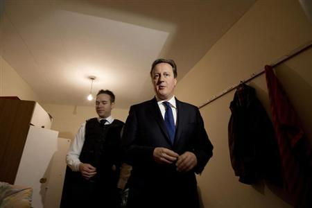 Britain's Prime Minister David Cameron is shown around a house that was raided earlier in the day by Immigration officers, in Southall, west London