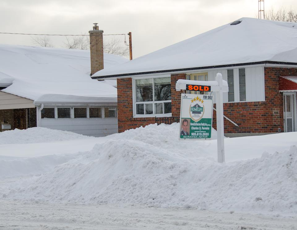 TORONTO, CANADA - 2014/02/06: Real State property or house for sale during a harsh Winter in Toronto, you can see the large pile of snow in the front after the superstorm or polar vortex hit the city in 2014. (Photo by Roberto Machado Noa/LightRocket via Getty Images)