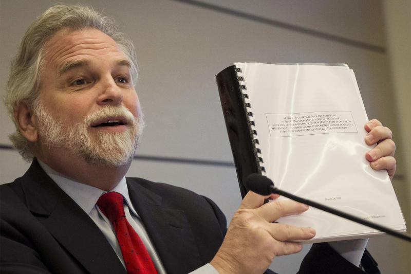 Attorney Randy Mastro holds up a copy of his report during a news conference, Thursday, March 27, 2014, in New York. Mastro, with the law firm hired by New Jersey Gov. Chris Christie, said that the governor was not involved in a plot to create gridlock near a major bridge as part of a political retribution scheme. (AP Photo/Brendan McDermid, Pool)