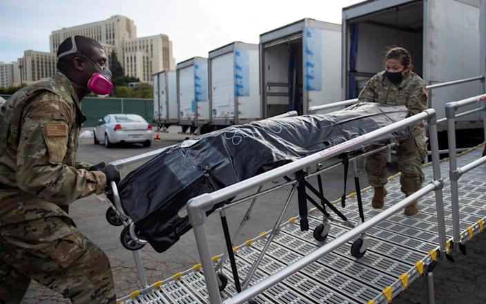 California National Guard personnel wheel a deceased person lying on a gurney to a secondary temporary refrigerated storage facility - REUTERS
