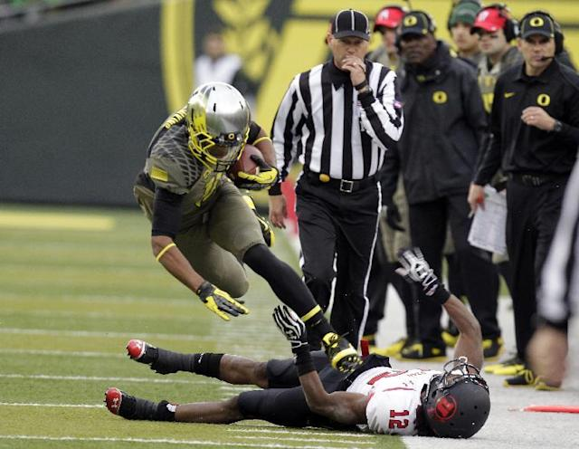 Oregon wide receiver Daryle Hawkins, left, leaps over Utah defender Justin Thomas on a run down the sideline during the second half of an NCAA college football game in Eugene, Ore., Saturday, Nov. 16, 2013. Oregon won 44-21. (AP Photo/Don Ryan)