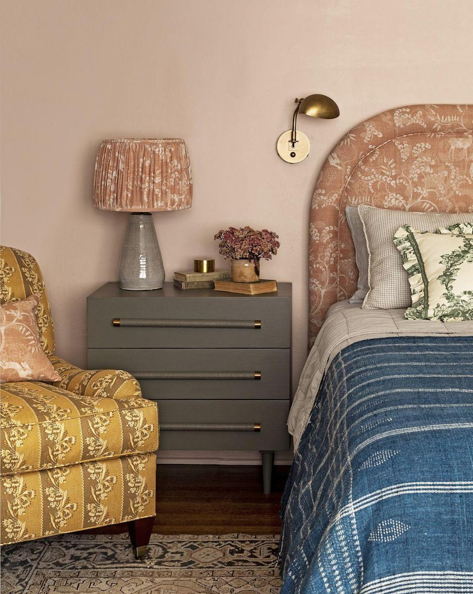 """<p> You know that old trick about pink lightbulbs offering more flattering light? Well, the same goes for a soft pinkish-orange paint color. Here, in this bedroom by <a href=""""https://heidicaillierdesign.com/wp-content/uploads/2020/01/Heidi-Caillier-Design-Seattle-interior-designer-Country-Living-N28-Tudor.pdf"""" rel=""""nofollow noopener"""" target=""""_blank"""" data-ylk=""""slk:designer Heidi Caillier"""" class=""""link rapid-noclick-resp"""">designer Heidi Caillier</a>, an earthy lamp base, clean-lined sconce, indigo bedspread, and modern moss green nightstand offset all things rosy and ruffled.</p><p><strong>Get the Look: </strong><br>Wall Paint Color: <a href=""""https://go.redirectingat.com?id=74968X1596630&url=https%3A%2F%2Fwww.farrow-ball.com%2Fen-us%2Fpaint-colours%2Fsetting-plaster&sref=https%3A%2F%2Fwww.countryliving.com%2Fremodeling-renovation%2Fhome-makeovers%2Fg32468539%2Fbest-bedroom-paint-colors-ideas%2F"""" rel=""""nofollow noopener"""" target=""""_blank"""" data-ylk=""""slk:Setting Plaster by Farrow & Ball"""" class=""""link rapid-noclick-resp"""">Setting Plaster by Farrow & Ball</a></p>"""