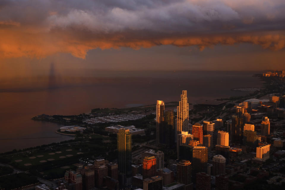 The shadow of the Willis Tower, left, falls on Lake Michigan and passing storm clouds as the setting sun lights up the Chicago skyline as seen from the Willis Tower, Tuesday, June 29, 2021. (AP Photo/Shafkat Anowar)