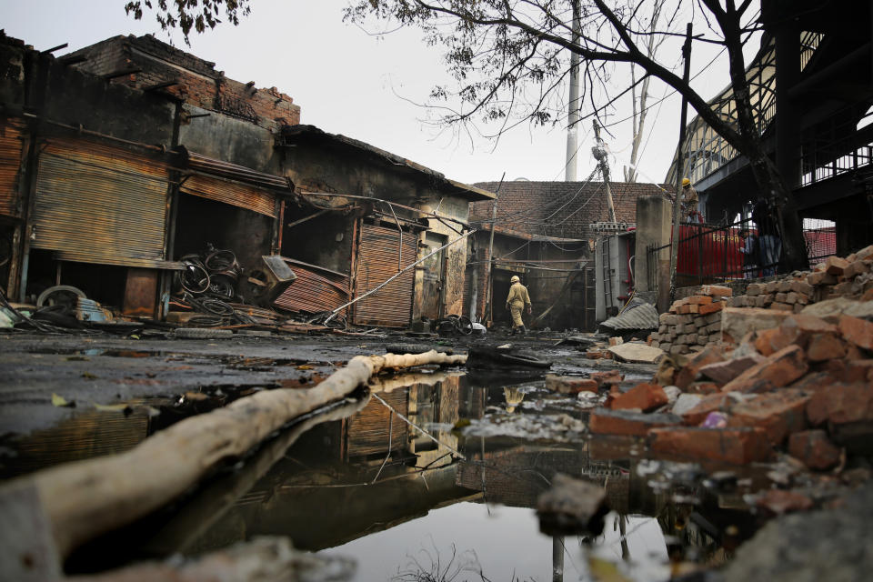 A fire fighter walks at the Gokul Puri tyre market which was burnt in Tuesday's violence in New Delhi, India, Wednesday, Feb. 26, 2020. At least 20 people were killed in three days of clashes in New Delhi, with the death toll expected to rise as hospitals were overflowed with dozens of injured people, authorities said Wednesday. The clashes between Hindu mobs and Muslims protesting a contentious new citizenship law that fast-tracks naturalization for foreign-born religious minorities of all major faiths in South Asia except Islam escalated Tuesday. (AP Photo/Altaf Qadri)