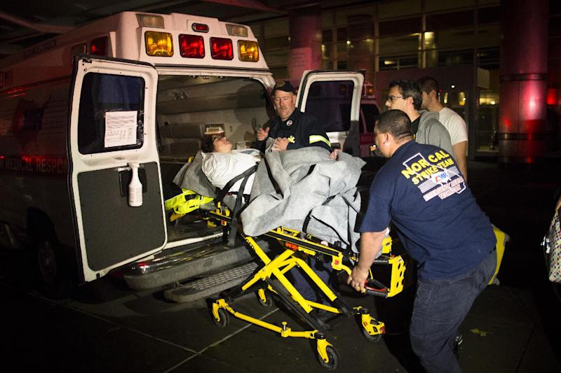Medical workers assist a patient into an ambulance during an evacuation of New York University Tisch Hospital, after its backup generator failed when the power was knocked out by a superstorm, Monday, Oct. 29, 2012, in New York. Dozens of ambulances lined up outside NYU Tisch Hospital on Monday night as doctors and nurses began the slow process of taking people out. (AP Photo/John Minchillo)