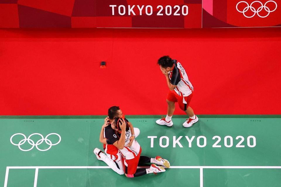 Greysia Polii (bottom right) and Apriyani Rahayu (top) of Indonesia celebrate with their coach Eng Hian.