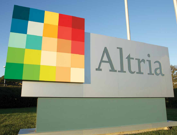 Altria logo sign in front of a grass field with trees on a clear day.