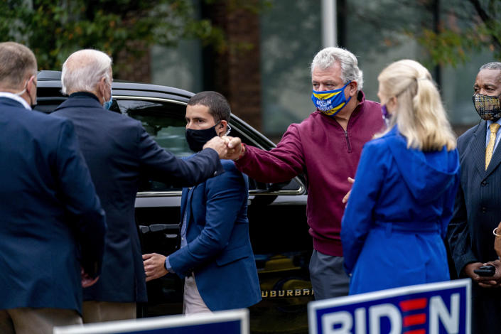 Democratic presidential candidate former Vice President Joe Biden fist bumps a supporter as he leaves after visiting people outside a voter service center, Monday, Oct. 26, 2020, in Chester, Pa. (AP Photo/Andrew Harnik)