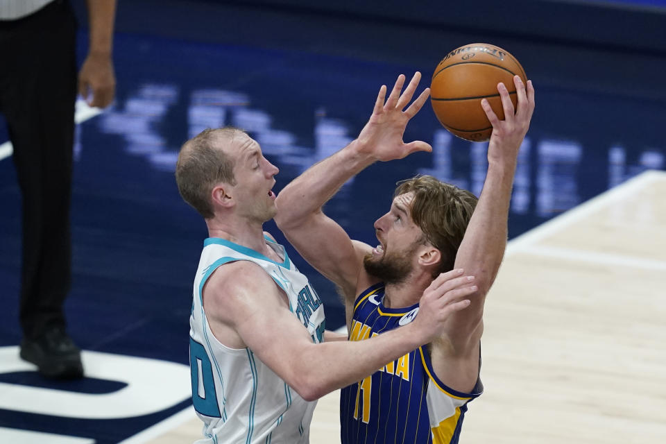 Indiana Pacers' Domantas Sabonis (11) goes to the basket against Charlotte Hornets' Cody Zeller (40) during the first half of an NBA basketball Eastern Conference play-in game Tuesday, May 18, 2021, in Indianapolis. (AP Photo/Darron Cummings)