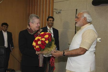 U.S. ambassador to India Nancy Powell (2nd L) receives a bouquet from Hindu nationalist Narendra Modi (R), prime ministerial candidate for India's main opposition Bharatiya Janata Party (BJP) and Gujarat's chief minister, during their meeting in Gandhinagar in the western Indian state of Gujarat February 13, 2014. REUTERS/Gujarat Information Department/Handout via Reuters