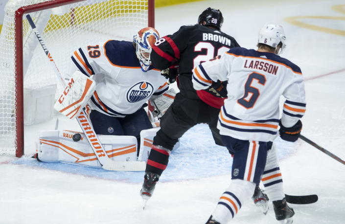 Edmonton Oilers goaltender Mikko Koskinen makes a pad save under pressure from Ottawa Senators right wing Connor Brown as Oilers defenseman Adam Larsson watches during the second period of an NHL hockey game Wednesday, April 7, 2021, in Ottawa, Ontario. (Adrian Wyld/The Canadian Press via AP)