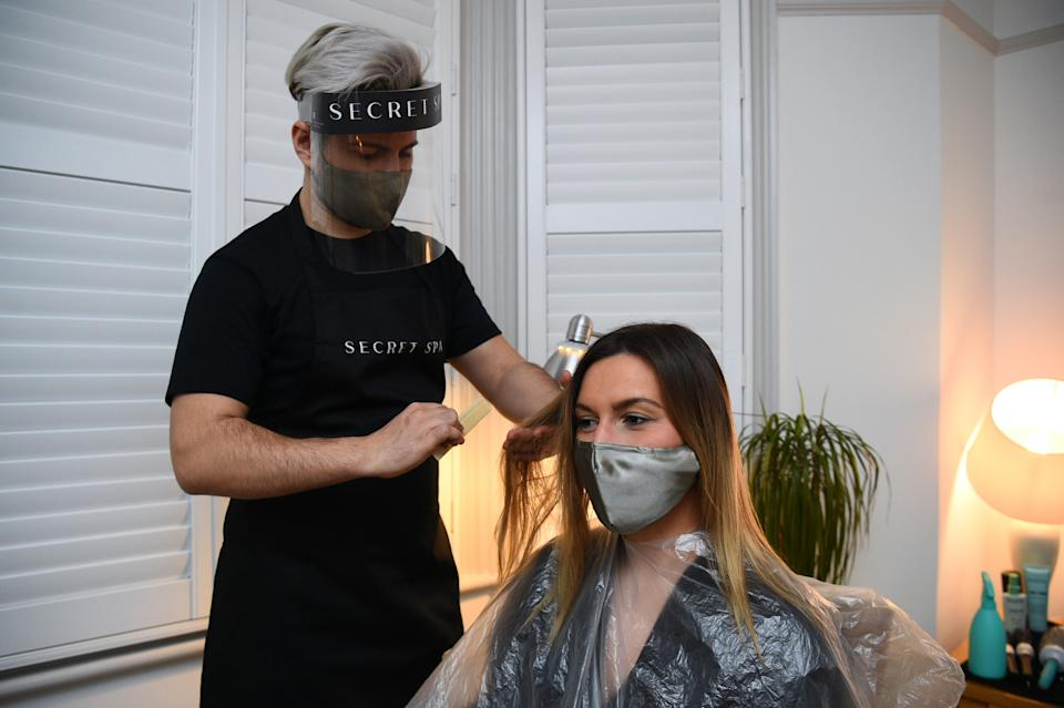 Secret Spa hair stylist Nas Ganev cuts the hair of Amy Pallister, 27, just after midnight at her home in Balham, south London. Five housemates desperate for a trim and tan booked Secret Spa stylist Nas Ganev and tan artist Magdelaine Gibson to visit their home at one minute past midnight for haircuts and bronzed skin as coronavirus restrictions eased across England. Secret Spa, which offers at-home beauty and wellness services in London, Manchester and Brighton, have extended their opening hours to accommodate 350 beauty treatments on the first day of restrictions lifting, with the first appointments beginning at one minute past midnight. Picture date: Monday April 12, 2021.