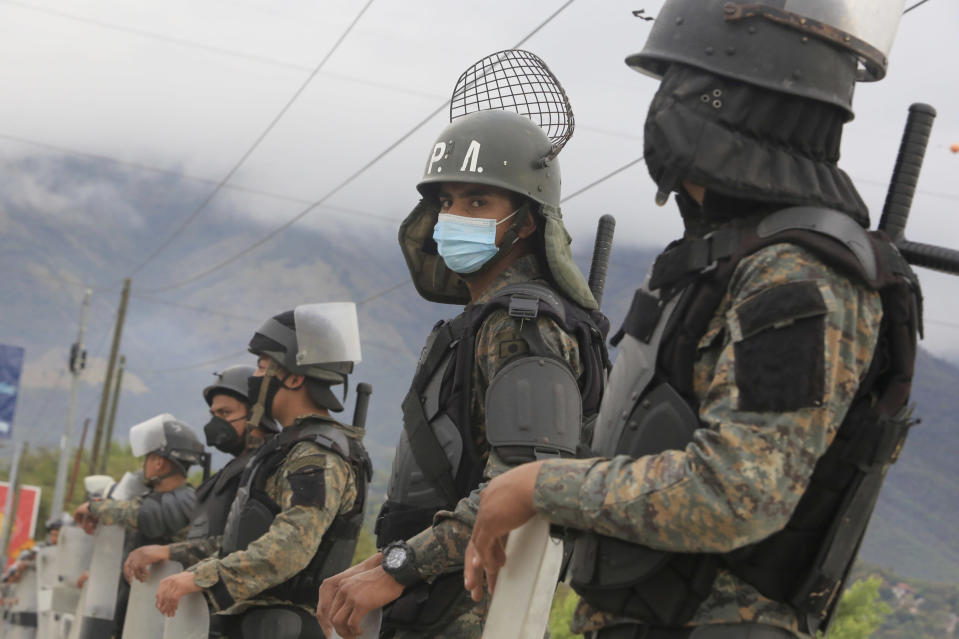 Guatemalan soldiers stands guard at a police checkpoint on the Motagua River to stop the advance of Honduran migrants in Zacapa, Guatemala, Tuesday, Jan. 19, 2021. A once large caravan of Honduran migrants that pushed its way into Guatemala last week had dissipated by Tuesday in the face of Guatemalan security forces. (AP Photo/Oliver de Ros)