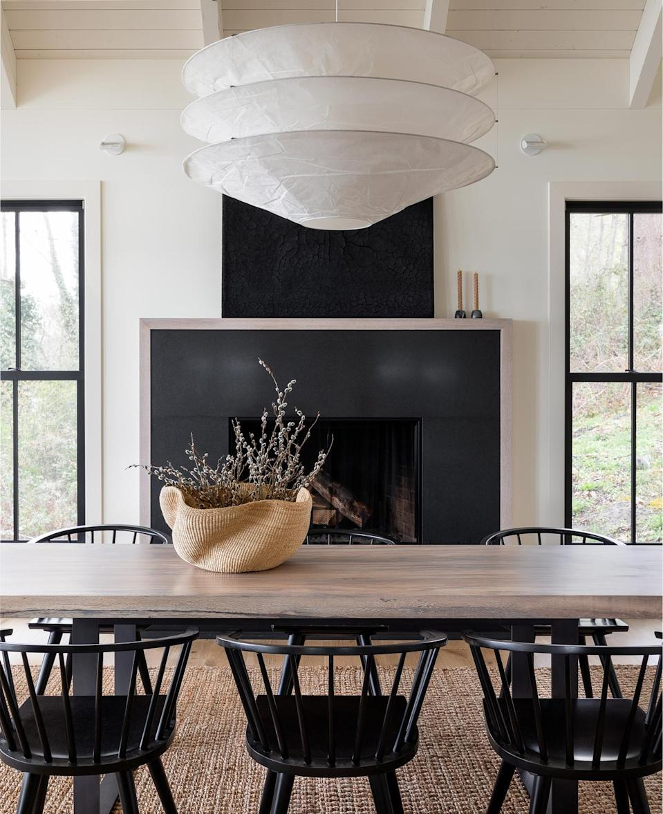 """<p>""""The client specifically <a href=""""https://www.marthastewart.com/1537032/fireplace-guide"""" rel=""""nofollow noopener"""" target=""""_blank"""" data-ylk=""""slk:requested the fireplace"""" class=""""link rapid-noclick-resp"""">requested the fireplace</a> in the dining room—it was a detail that existed in the house he grew up in. It felt nostalgic and added warmth to that space,"""" says Beers. """"The table is a single slab of Oregon white oak, which looks amazing. And we love the dining chairs, which are several sets of vintage chairs combined and refinished with black lacquer.""""</p>"""