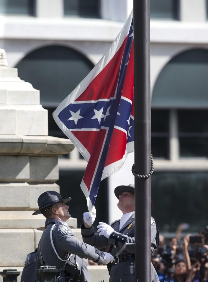 FILE - In a Friday, July 10, 2015 file photo, an honor guard from the South Carolina Highway patrol removes the Confederate battle flag from the Capitol grounds in Columbia, S.C., ending its presence there. One big change happened in conservative South Carolina after a racist gunman killed nine black people during a Bible study five years ago -- the Confederate flag came down. But since then, hundreds of other monuments and buildings named for Civil War figures, virulent racists and even a gynecologist who did painful, disfiguring medical experiments on African American women remain. (AP Photo/John Bazemore, File)