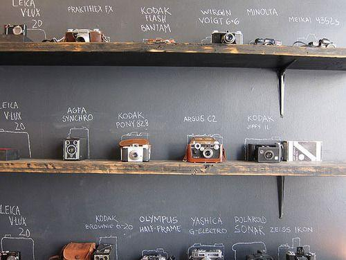 Displaying cameras in front of a chalkboard is a genius way to keep an  inventory of what you have. (And to look smart when people asking you  what's what.)