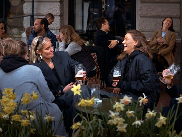 People chat and drink in Stockholm, Sweden, April 8, 2020.