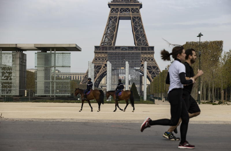 people jogging in Paris while police on horseback look on