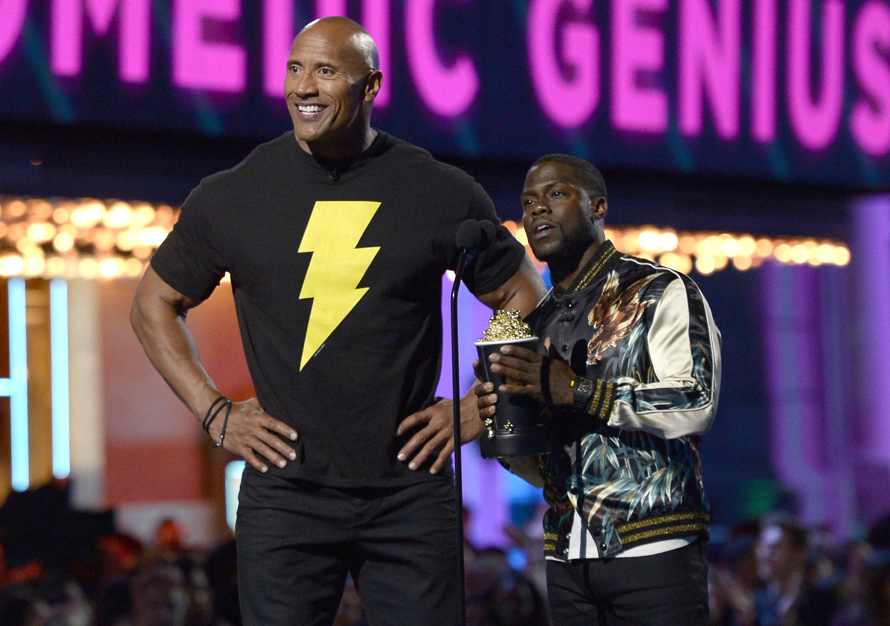 Dwayne Johnson, left, and Kevin Hart present the best comedic genius award at the MTV Movie Awards at Warner Bros. Studio on Saturday, April 9, 2016, in Burbank, Calif. (Kevork Djansezian/Pool Photo via AP)
