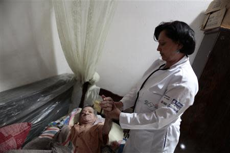 Cuban doctor Elisa Barrios Calzadilla inspects a patient during a house call in the city of Itiuba in the state of Bahia, northeastern Brazil