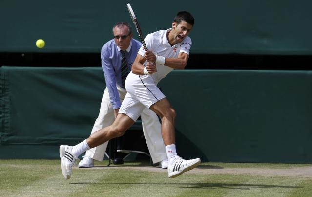 Novak Djokovic of Serbia hits a return during his men's singles final tennis match against Roger Federer of Switzerland at the Wimbledon Tennis Championships, in London July 6, 2014. REUTERS/Suzanne Plunkett (BRITAIN - Tags: SPORT TENNIS)