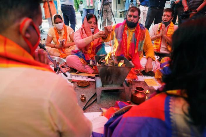 """Hindu priests and supporters of the Vishva Hindu Parishad (VHP), a Hindu nationalist organisation, perform """"havan"""" (traditional Hindu fire ritual) as part of a special prayer for a stone laying ceremony of the Ram Temple in Ayodhya"""