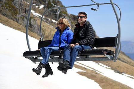 Emmanuel Macron, head of the political movement En Marche ! (Onwards !) and candidate for the 2017 presidential election, and his wife Brigitte Trogneux sit on a chairlift on their way to the mountain top for a lunch break during a campaign visit in Bagneres de Bigorre, in the Pyrenees mountain, France, April 12, 2017.  REUTERS/Eric Feferberg/Pool