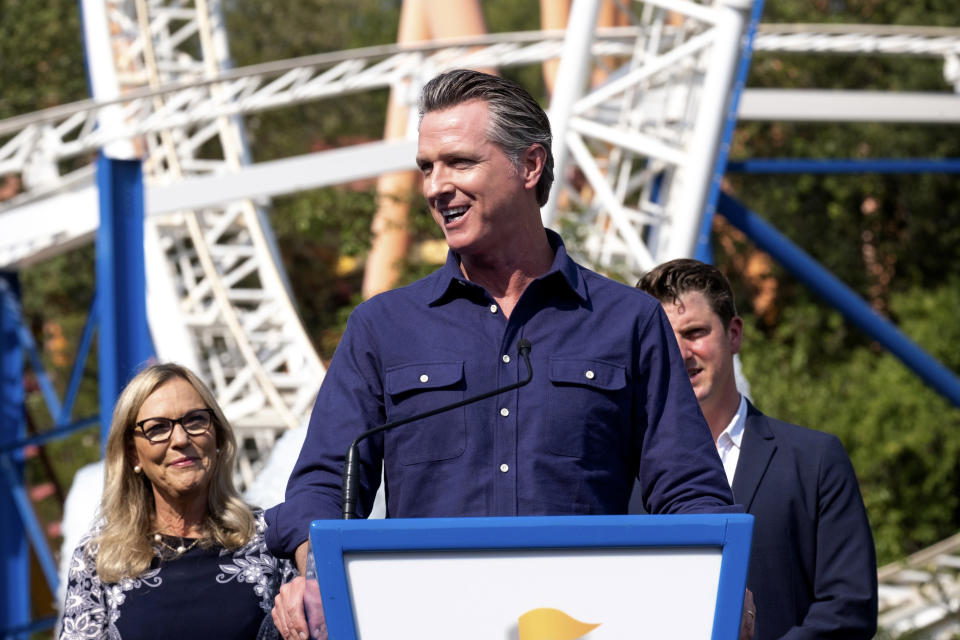 California Governor Gavin Newsom welcomes the public to Six Flags Magic Mountain in Santa Clarita, Calif., on Wednesday, June 16, 2021. In background are Los Angeles County Supervisor Kathryn Barger and state Sen. Henry Stern. Newsom continued his tour of the state after lifting most COVID-19 restrictions Tuesday. (David Crane/The Orange County Register via AP)