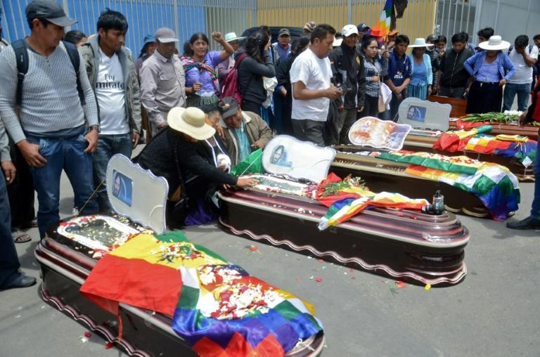 Relatives mourn by the coffins of protesters killed during protests in the Bolivian town of Sacaba on November 16, 2019