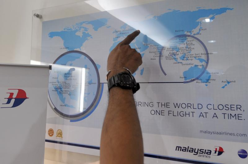 A man points at a world map at a Malaysia Airlines office in Jakarta on July 18, 2014, after flight MH17 was allegedly shot down in Ukraine (AFP Photo/Bay Ismoyo)