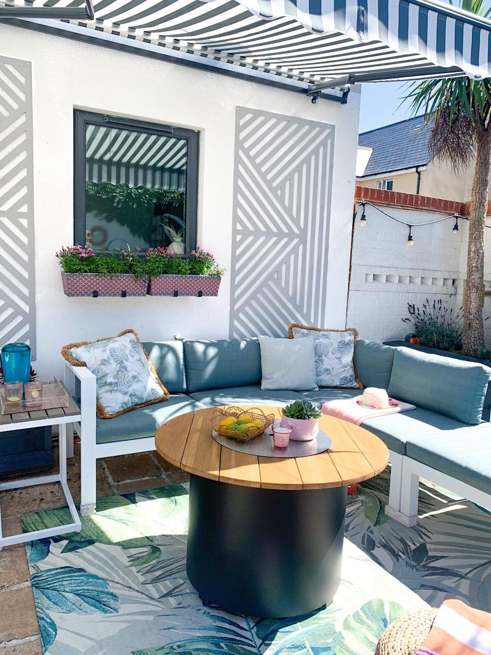 <p>How inviting does this outdoor seating area look? From the garden cushions to the tropical rug, it's the perfect place for whiling away a lazy summer's afternoon. </p>