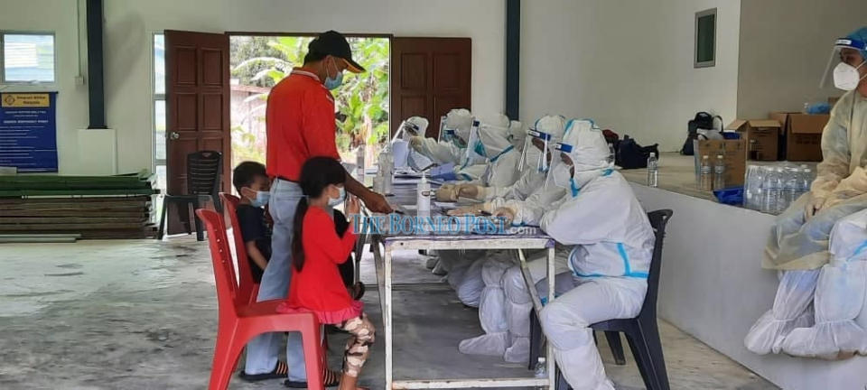 Medical frontliners taking down particulars from those coming for swab tests at a community hall recently. — Borneo Post Online pic